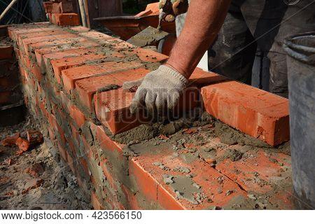 Masonry Construction. A Mason Person, A Bricklayer Is Laying, Installing Bricks, Using A Mortar And