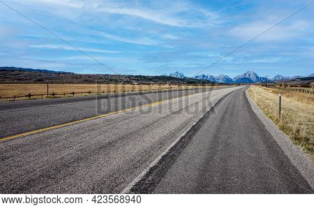 Road With A Diminishing Perspective  Leading Through The Dramatic Wyoming Landscape.