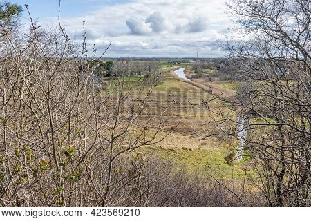 Dutch Countryside With A Stream Between Farmland And Farms, Seen From A Hill With Bare Trees, Spring