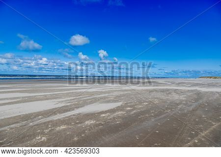 White Sandy Beach, The Sea With Calm Waves In The Background, Sunny Day With A Blue Sky With Abundan