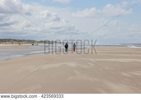 People Walking On The Beach With Remnant Of Water Between The Sea And The Dunes, Day With A Blue Sky