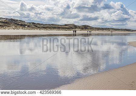 Beach, Water Reflecting White Clouds, People Walking With Dunes In The Background, Cloudy Day With A