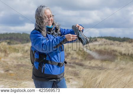 Funny Scene Of A Mature Woman Taking The Sand Out Of Her Shoe, Hill With White Sand And Wild Grass,