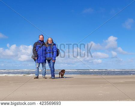 Happy Mature Couple, Mexican Woman And A Dutch Man With Their Brown Short Hair Dachshund Enjoying Th