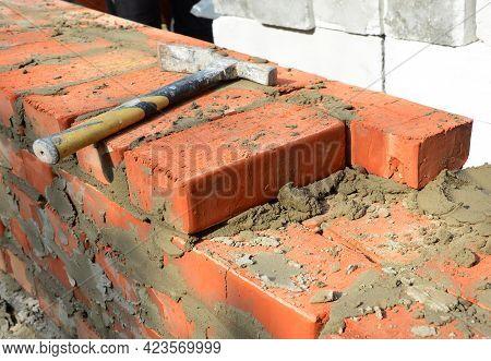 Masonry Tools And Equipment. A Close-up Of A Masonry Wall Construction Using A Bricklayer's Hammer,