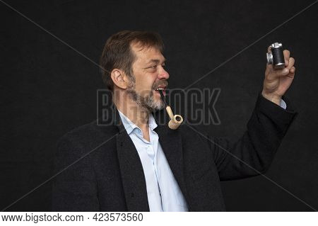 Portrait Of An Elderly Man 45-50 Years Old With A Pipe In His Mouth And A Black Coat On A Dark Backg