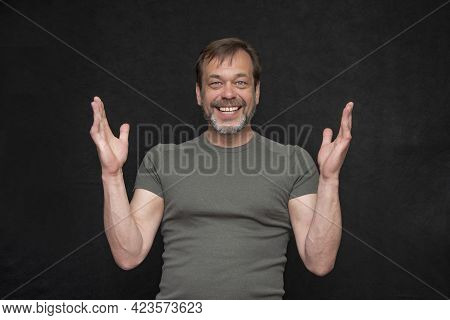 Portrait Of A Laughing Man 45-50 Years Old With A Gray Beard And A Green T-shirt With Outstretched A