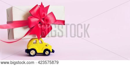 Yellow Toy Retro Car With Gift Box On A Roof On Pink Background. Copy Space
