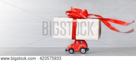 Red Toy Retro Car With Gift Box On A Roof On Gray Background. Copy Space