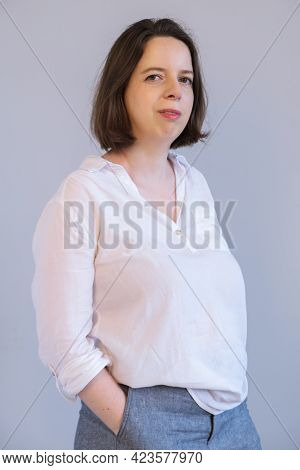 Vertical Portrait Of A Young Brunette Woman In White Shirt And Gray Trousers On Gray Wall Background