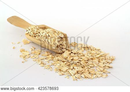 Oat Flakes In Wooden Spoon Isolated On White Background. Heap Of Oats For Package Of Oatmeal Or Gran