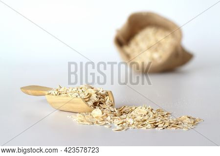 Oat Flake In A Sack And Spoon On The White Background. Heap Of Oats For Package Of Oatmeal Or Granol