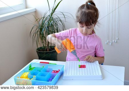 The Girl Plays The Children's Educational Constructor Puzzle With A Screwdriver, A Screwdriver And S