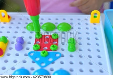 Close-up Of A Child Playing A Childrens Educational Constructor Puzzle With A Screwdriver, A Screwdr