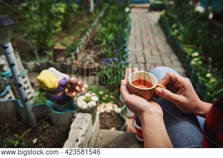 Close-up Of A Ceramic Cup With Tea In Female Gardener Hands On The Background Of A Garden In Country