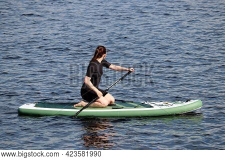 Girl In Black Wetsuit With Paddle Kneeling Down On A Board In A Water. Standup Paddleboarding, Summe