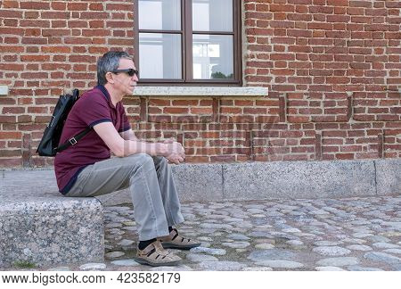 Close-up Of An Adult Pensioner In Summer Clothes And With A Backpack Sits And Rests Against The Back