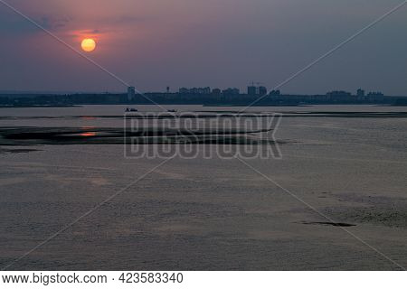 Sunset Over The City By The River. Orange Sun Over The City.