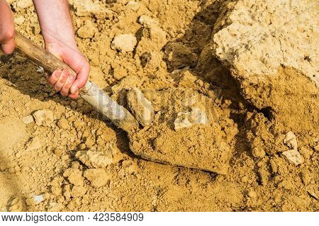 Close Up Of Hand Of A Builder Picks Up Sand For Mortar With A Shovel. Making Concrete Screed Or Plas