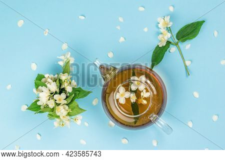 Teapot With Jasmine Tea And Jasmine Flowers On A Blue Background. An Invigorating Drink That Is Good