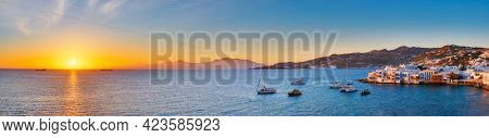 Sunset panorama of Mykonos island, Greece with yachts in the harbor and colorful waterfront houses of Little Venice romantic spot on sunset with cruise ship and yacht boats. Mykonos townd, Greece