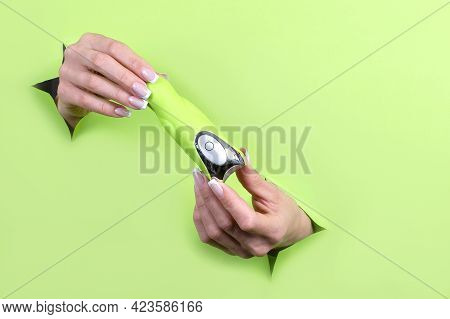 Female Hands Holding Sex Toys On A Green Background. Sex Shop Concept.