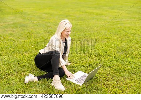 Young Woman Using Laptop In The Park