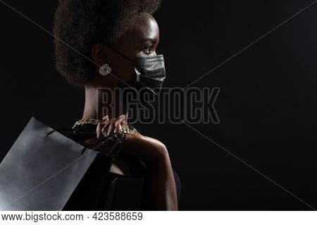 Profile View Of African American Woman In Black Medical Face Mask Holds Black Shopping Bags. Safety