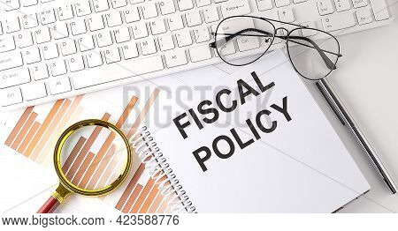 Fiscal Policy Text Written On The Notebook With Keyboard, Chart,and Glasses