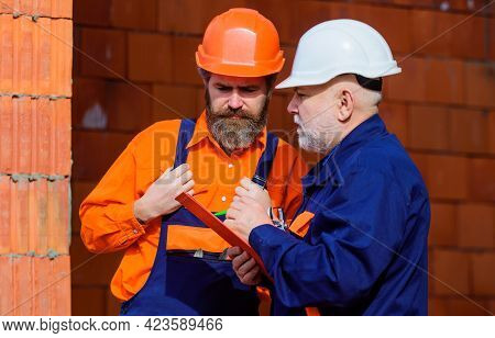 Two Workers With Helmets And Builder Uniform In Construction Site. Professional Builders On Work.