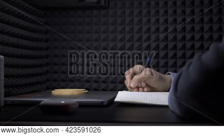 Man Writes In Notebook On Background Of Black Wall. Hdr. Young Man Writes Music In Notebook. Man Wri