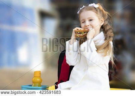 Cute Little Girl Eating Sandwich During Break Between Classes. Healthy Unhealthy Food For Kid. Break