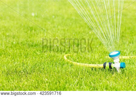 Automatic Lawn Watering Green Grass. Sprinkler With Automatic System. Irrigation Of The Garden. Wate