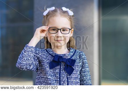 Portrait Of Beautiful Little Girl Wearing Glasses In Blue Lifestyle Background. Poor Eyesight In Chi