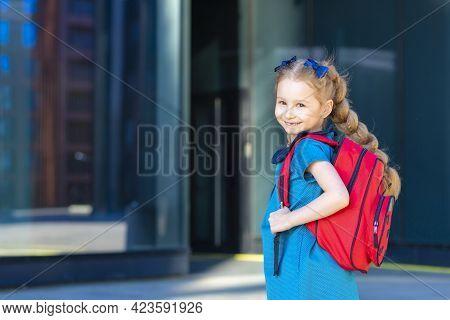 Beautiful Kid Back To School. Happy Cute Confident Girl In Uniform. Schoolchild In Blue Dress With R