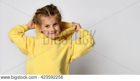Portrait Of A Joyful Active Little Girl Wearing A Hood On A White Background. Happy Cute Child In A