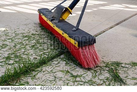 Push Broom Sweeping Grass Clippings Off Patio