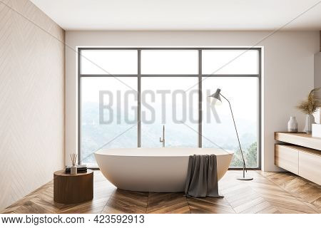 Minimalistic White And Wooden Bathroom Interior With White Bathtub, Sink And Window With Blurry Moun