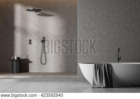 Grey Bathroom Interior With White Tub And Grey Towel, Concrete Floor And Stylish Shower. Modern Bath