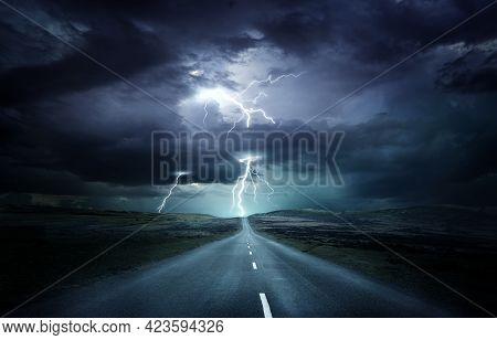 Extreme Weather Conditions. An Empty Landscape With A Road Leading Into A Powerful Thunderstorm With