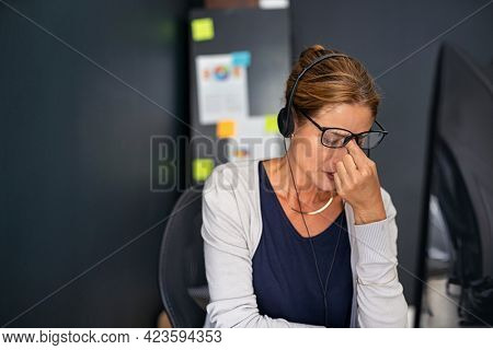 Upset businesswoman suffering from headache while working from home. Tired mature woman suffering from migraine after conversation with a client. Middle aged woman feeling unhappy working from home.