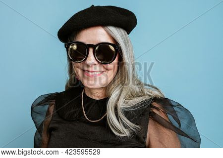 Beautiful senior woman in a cool beret and sunglasses