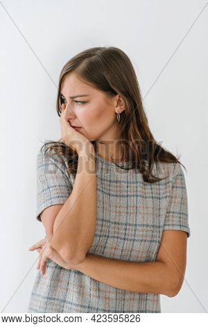 Stressed woman in a gray plaid dress