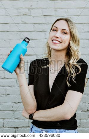 Happy woman carrying a thermal bottle