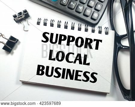 Business Concept.text Support Local Business On Notebook With Paper Clips,calculator And Glasses On