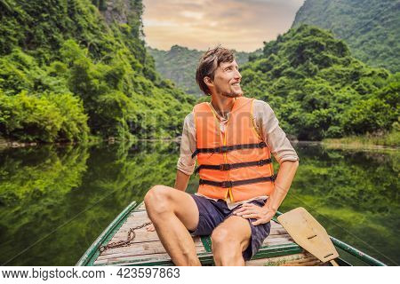 Man Tourist In Trang An Scenic Landscape Complex In Ninh Binh Province, Vietnam A Unesco World Herit