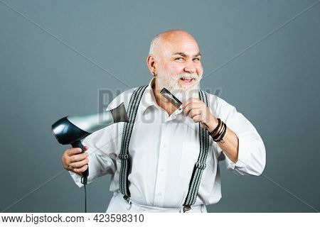 Happy Senior Hairdresser Barber With Hair Dryer And Comb Drying Beard And Moustache. Portrait Of Old