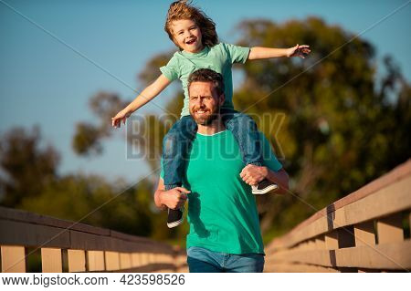 Father Giving Son Ride On Back In Park. Portrait Of Happy Father Giving Son Piggyback Ride On His Sh