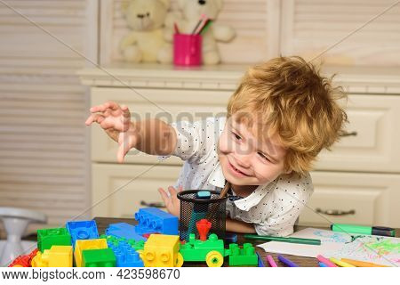 Child In Playroom. Kids Face, Little Boy Playing With Colorful Blocks, Portrait.
