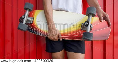 Closeup Surfskates Board In The Hands Of Teenager In A Hip Position, In Front Of Red Galvanized Stee